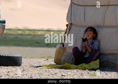 Mongolische Mädchen mit zwei Zöpfen sitzt tief versunken im Schatten des mongolischen Ger oder Jurte und spielt - Stockfoto