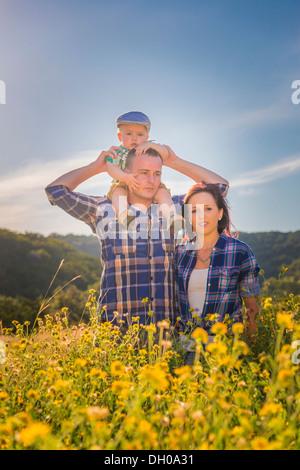 Eine kaukasische Familie, Vater, Mutter und Kind Junge auf Papas Schultern, zu Fuß durch ein Feld von gelben Wildblumen. - Stockfoto