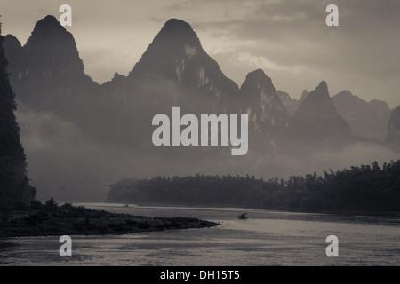 Ein einsamer Boot auf dem Li-Fluss zwischen Karst Peaks in Süd-China - Stockfoto