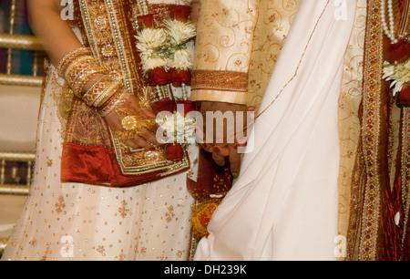 Braut und Bräutigam gekleidet in all ihrer Pracht ihrer traditionellen Hindu Hochzeit feiern.