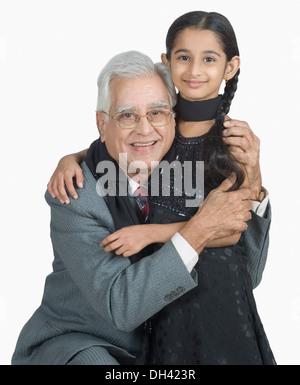 Ältere Mann umarmt seine Enkelin und lächelnd - Stockfoto