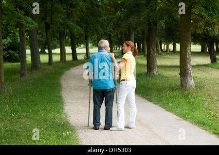 Frau und ein älterer Mann auf Krücken spazieren im park - Stockfoto