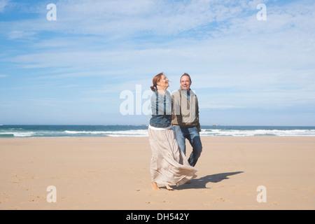 Paar am Strand entlang spazieren - Stockfoto