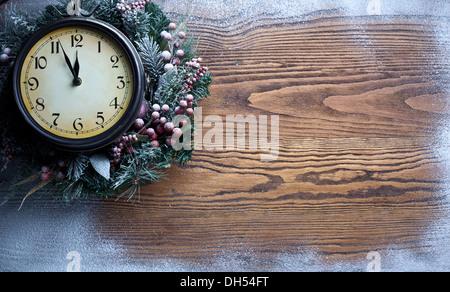 Neujahr-Uhr über Schnee hölzernen Hintergrund. Fünf vor zwölf. - Stockfoto