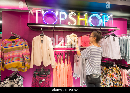 Junge Frau einkaufen in Topshop, Oxford Street, London, England, UK - Stockfoto