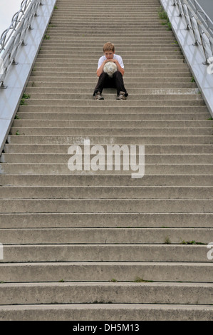 Einsame 10 - jähriger Junge mit seinem Fußball sitzt auf der Treppe auf die Aussichtsplattform des Schokoladenmuseum, - Stockfoto