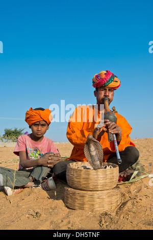 Rajasthani Schlangenbeschwörer mit einem Turban, eine Querflöte, eine Kobra oder Naja Wicklung aus einem Korb vor - Stockfoto