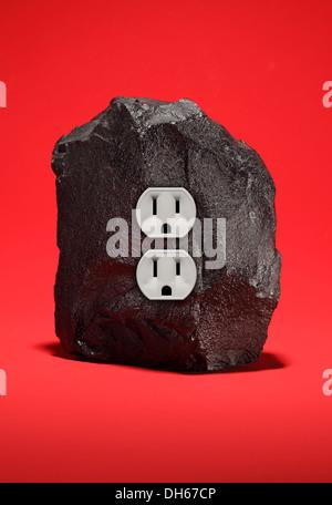 Ein großes Stück Steinkohle mit einer doppelten Steckdose. Leuchtend roten Hintergrund - Stockfoto