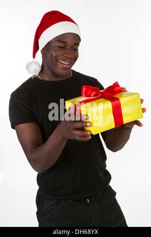 Junger schwarzer Mann trägt eine Weihnachtsmütze und hält ein Geschenk - Stockfoto