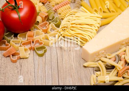 Verschiedene italienische Pasta, Pecorino und rote Tomate auf Holz - Stockfoto