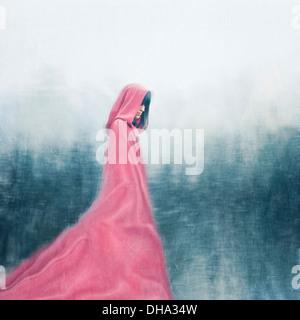 Frau mit roten Umhang walking im freien - Stockfoto