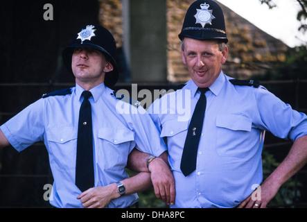 Kleine und große geformte UK Polizisten posieren die anderen Offiziere Helm zu tragen. - Stockfoto
