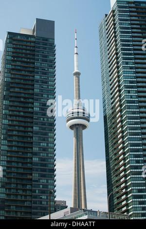 CN Tower eingerahmt zwischen zwei Wolkenkratzern und blauer Himmel; Toronto, Ontario, Kanada - Stockfoto