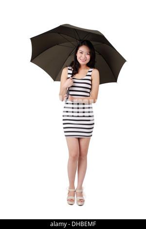 Junge Frau in einem gestreiften Kleid hält einen Regenschirm - Stockfoto