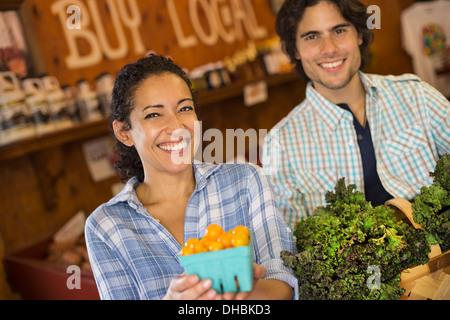 Zwei Personen mit Körben von Tomaten und geschweiften grünes Blattgemüse. Arbeiten auf einem Bio-Bauernhof. - Stockfoto