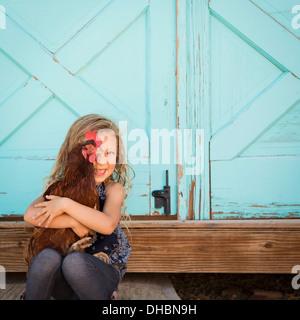 Ein junges Mädchen, ein Huhn auf dem Arm halten. - Stockfoto