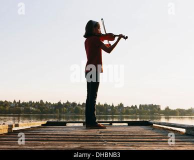 Ein zehn Jahre altes Mädchen, das Geigenspiel im Morgengrauen auf einem hölzernen Dock. - Stockfoto