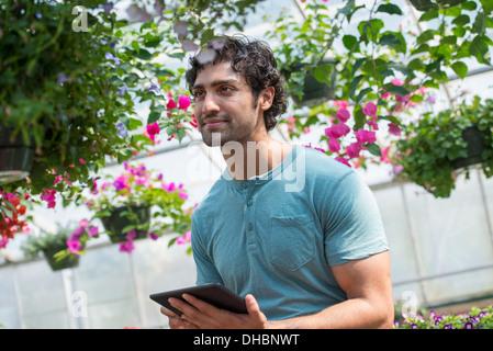 Ein junger Mann arbeitet in einer Gärtnerei, umgeben von blühenden Pflanzen. - Stockfoto