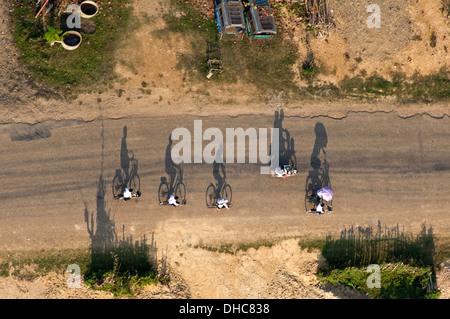 Horizontale Draufsicht des Menschen Reiten entlang der Straße auf Fahrrädern in Vang Vieng. - Stockfoto