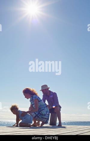 Weiblichen Kleinkind und Eltern kniend auf Pier, Utvalnas, Hotels, Schweden - Stockfoto