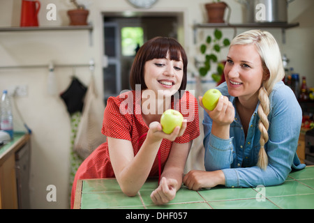 Zwei junge Frauen in Küche hält Äpfel - Stockfoto