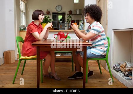 Junges Paar sitzt am Küchentisch - Stockfoto