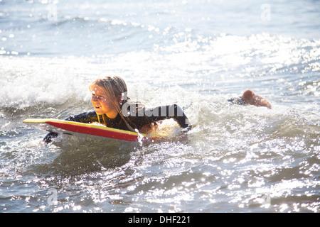 Porträt eines Mädchens auf Surfbrett, Wales, UK - Stockfoto