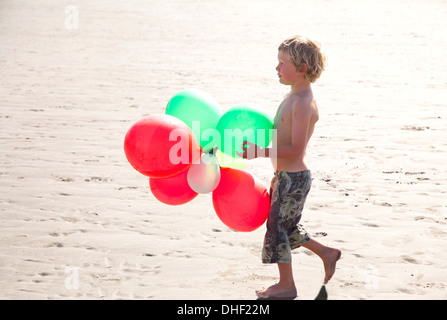 Boy am Strand mit Luftballons, Wales, UK - Stockfoto