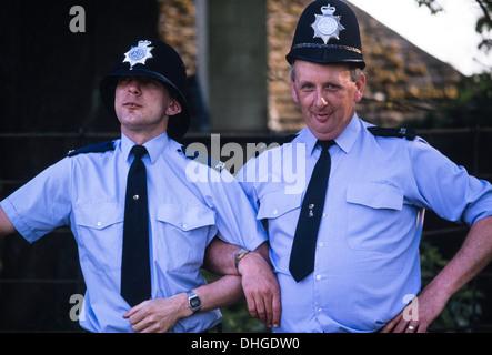 Ein paar britische Polizisten mit ihren Helmen über Hanteln - Stockfoto