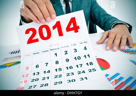 Mann in einem Anzug sitzt in einem Schreibtisch mit einem Stapel von Karten und zeigt einen Kalender 2014 - Stockfoto