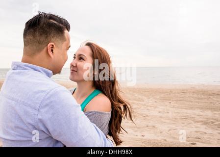 Junges Paar umarmt am Strand - Stockfoto