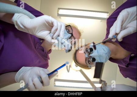 Zahnarzt und Zahnarzthelferin lehnt sich nach vorne halten Dentalgeräte Stockfoto