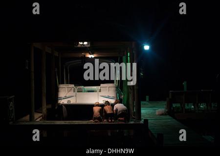 Drei Jungs spielen am Yachthafen in der Nacht, Shalimar, Florida, USA - Stockfoto