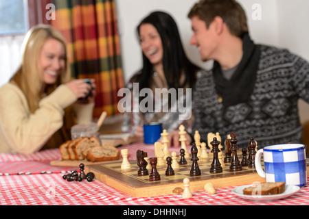 Schach spielen, gemütliche Winter Chalet Freunden Lachen Urlaub - Stockfoto