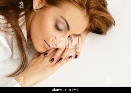 Junge Geschäftsfrau eingeschlafen am Bürotisch - Stockfoto