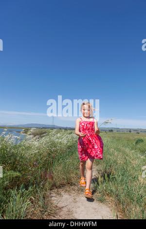 Mädchen zu Fuß von Fluss marsh - Stockfoto