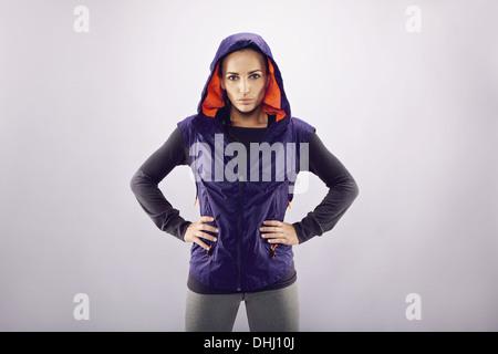 Porträt von zuversichtlich Sportlerin stehend mit den Händen auf den Hüften vor grauem Hintergrund mit Exemplar. - Stockfoto