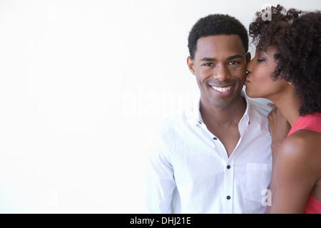 Porträt der jungen Frau, die Mann auf Wange küssen - Stockfoto