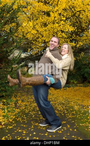 Vertikale Foto von Erwachsenen Brautpaar mit Mann mit seiner Frau eine Huckepack Reiten im Park während eines schönen - Stockfoto