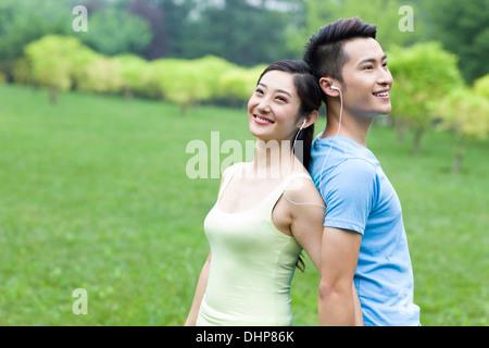 Süße junge Paar Musikhören im park - Stockfoto