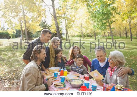 Glückselig Multi-Generation hören Reife Frau Grußkarte im Park lesen - Stockfoto