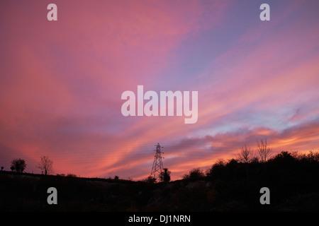 Roten Sonnenuntergang hinter einem Strommast - Stockfoto