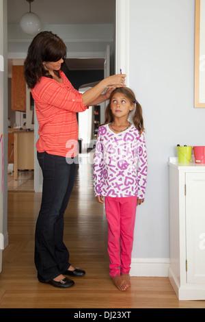 Maßnahmen eine Mutter ihre Tochter Höhe gegen A Wand zu Hause; San Francisco, Kalifornien, Vereinigte Staaten von - Stockfoto