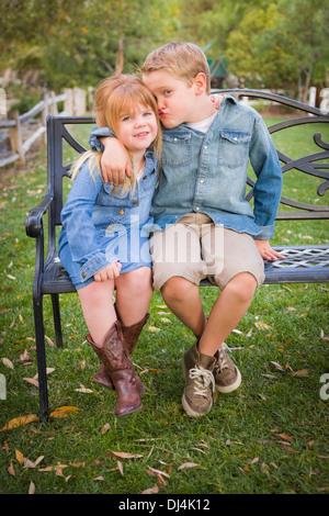 Happy Young Bruder und Schwester zusammen sitzen auf einer Bank außerhalb. - Stockfoto