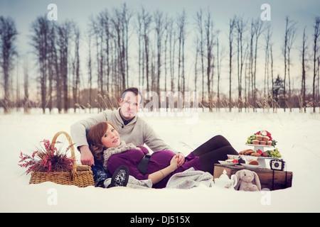Ein paar mit einem Winter-Picknick während der Schwangerschaft; Edmonton, Alberta, Kanada - Stockfoto