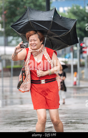 Chinesische Touristen mit einem gebrochenen Schirm fotografiert während eines tropischen Sturms in Hong Kong - Stockfoto