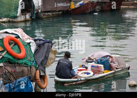 Chinesischer Mann sitzt auf einer überladenen Start in Causeway Bay Typhoon Shelter, Hong Kong. - Stockfoto