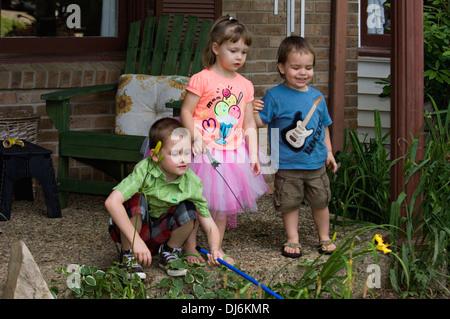 Fünf Jahre alten Bruder, drei Jahre alte Schwester und zwei Jahre alten Cousin spielen auf der Veranda des s-Bahn - Stockfoto
