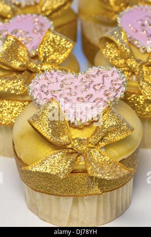 Geeiste Tasse Kuchen verziert mit rosa Herzen und goldenen Bögen. - Stockfoto