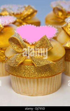 Cupcakes mit goldenen Zuckerguss verziert und Bögen auch rosa Herzen. - Stockfoto